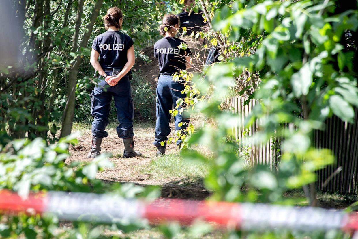 German police stand during a search in a garden allotment in the northern German city of Hanover on July 29, 2020, in connection with the disappearance of British girl Madeleine McCann. - Police resumed searching an allotment plot in Germany, with hopes high of some light finally being shed on the years-long mystery. Officers used sniffer dogs and an excavator as they dug up the site in the city of Hanover, with several police vehicles parked around a cordoned-off area. (Photo by Hauke-Christian Dittrich / AFP) (Photo by HAUKE-CHRISTIAN DITTRICH/AFP via Getty Images)