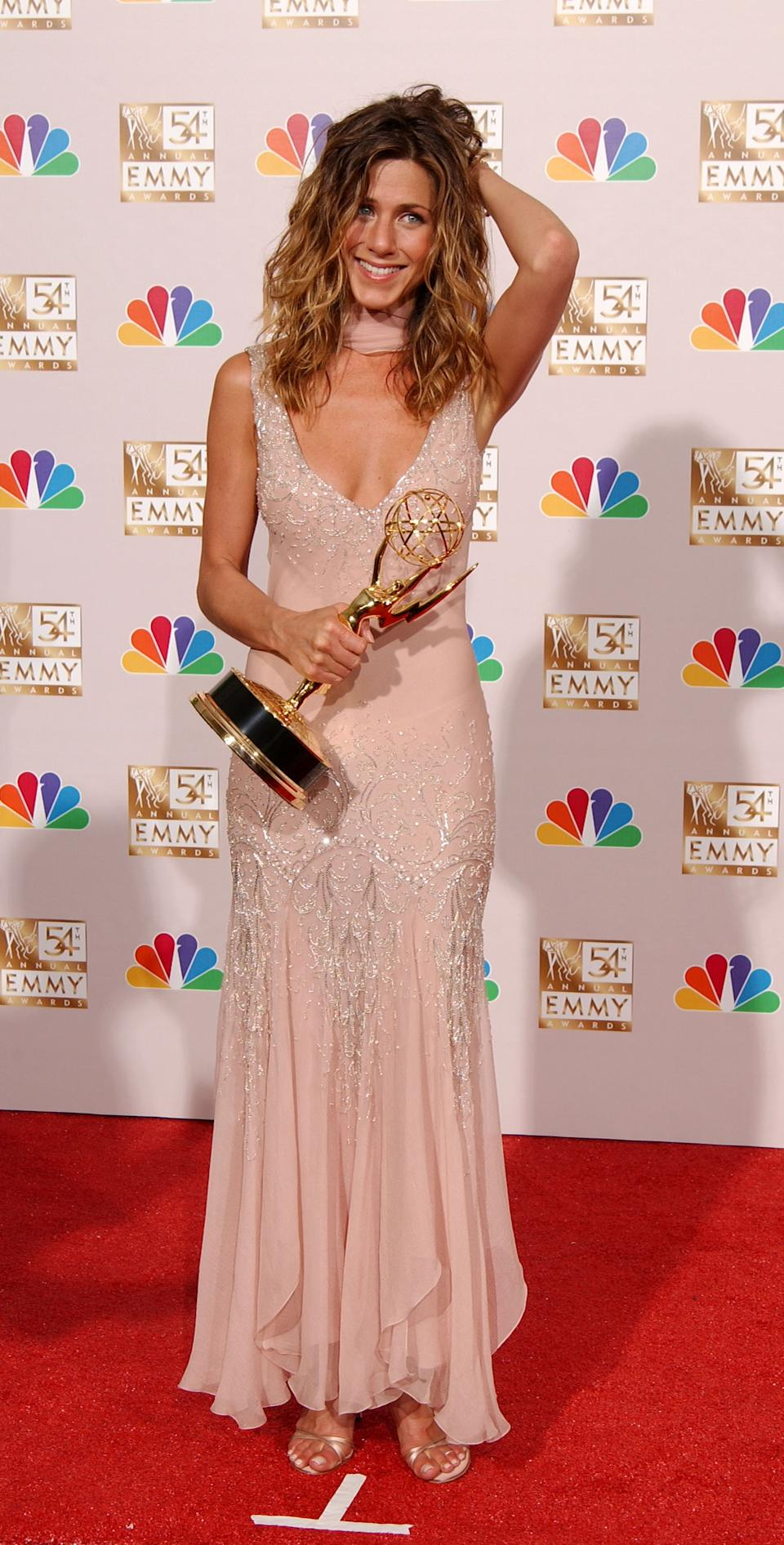 """Aniston accepted the award for """"Lead Actress in a Comedy Series"""" at the 2002 Emmy Awards wearing a blush Christian Dior gown. (Photo by Robert Mora/Getty Images)"""