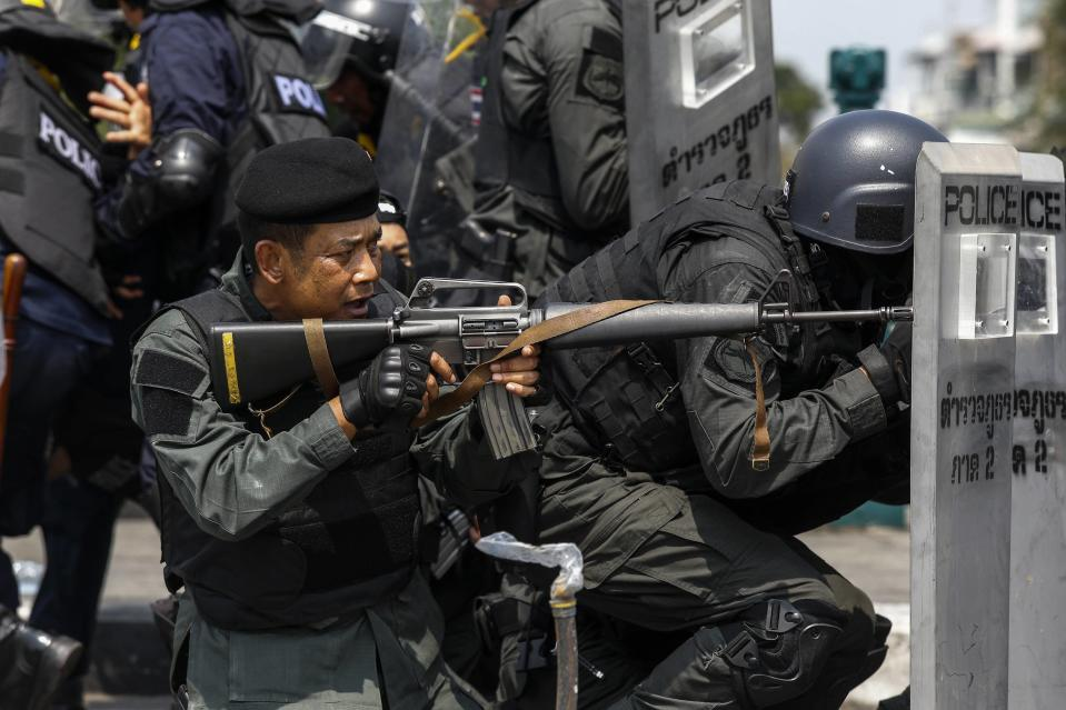 A Thai police officer aim his weapon towards anti-government protesters during clashes near Government House in Bangkok February 18, 2014. A Thai police officer was killed and dozens of police and anti-government protesters were wounded in gun battles and clashes in Bangkok on Tuesday, officials and witnesses said. REUTERS/Athit Perawongmetha (THAILAND - Tags: POLITICS CIVIL UNREST)