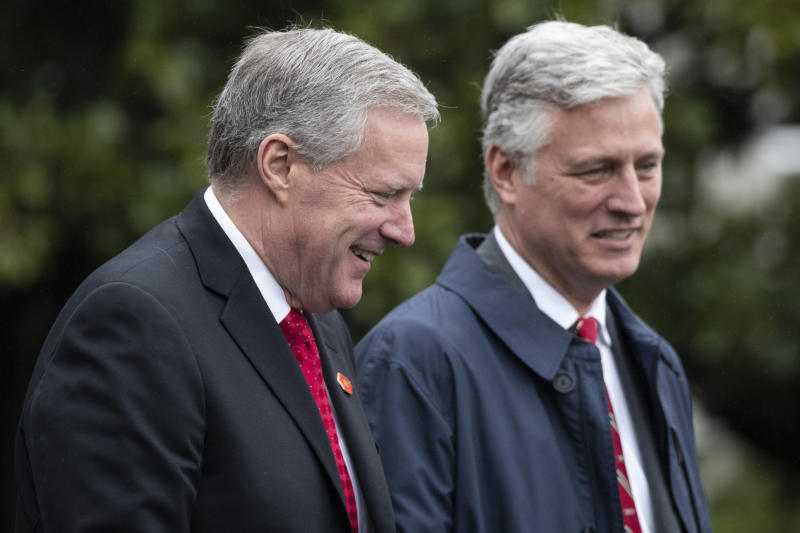 Acting White House Chief of Staff Mark Meadows, left, walks with National Security Adviser Robert O'Brien to join President Donald Trump on Marine One as he departs the White House, Saturday, March 28, 2020, in Washington. Trump is en route to Norfolk, Va., for the sailing of the USNS Comfort, which is headed to New York. (AP Photo/Alex Brandon)