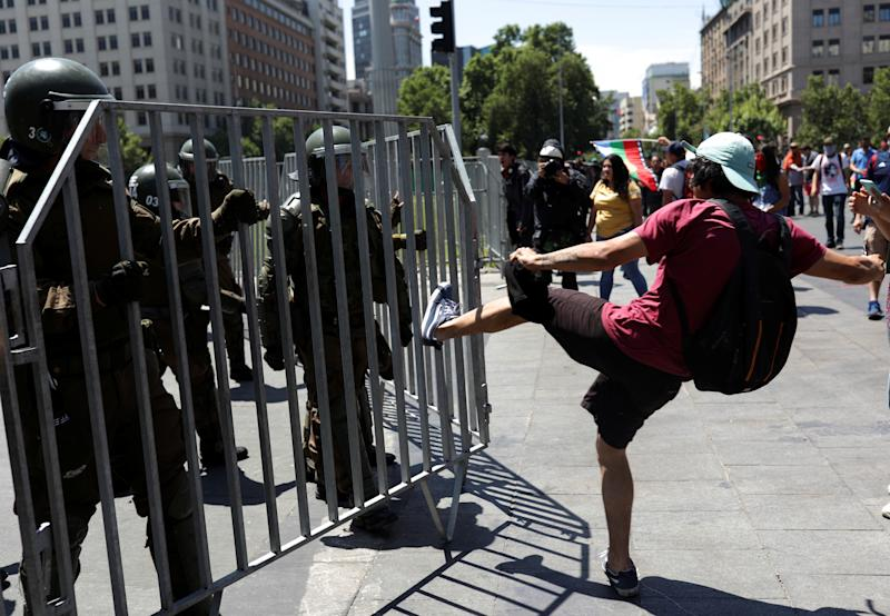 A demonstrator kicks a fence held by police officers during a protest against Chile's government in Santiago, Chile on Oct. 28, 2019. (Photo: Pablo Sanhueza/Reuters)