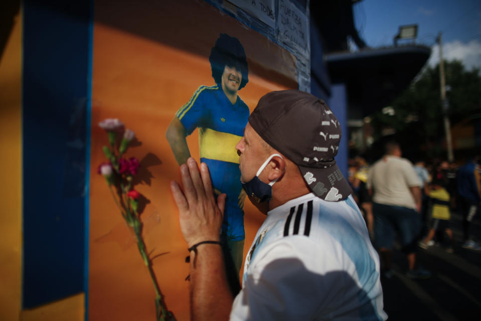 A soccer fan kisses a poster of Diego Maradona at the entrance of the Boca Juniors stadium, known as La Bombomera, in Buenos Aires, Argentina, Wednesday, Nov. 25, 2020. The Argentine soccer great who was among the best players ever and who led his country to the 1986 World Cup title before later struggling with cocaine use and obesity, died from a heart attack on Wednesday at his home in Buenos Aires. He was 60. (AP Photo/Natacha Pisarenko)