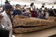A member of Egyptian archaeological team opens the sarcophagus is around 2500 years old at the Saqqara archaeological site, 30 kilometers (19 miles) south of Cairo, Egypt, Saturday, Oct. 3, 2020. Egypt says archaeologists have unearthed about 60 ancient coffins in a vast necropolis south of Cairo. The Egyptian Tourism and Antiquities Minister says at least 59 sealed sarcophagi with mummies inside were found that had been buried in three wells more than 2,600 years ago. (AP Photo/Mahmoud Khaled)