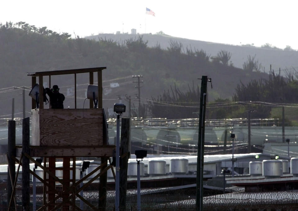 FILE - In this Sept. 10, 2002, file photo a U.S. Army military police officer looks through binoculars from a guard tower at Camp Delta where 598 detainees from some 43 countries are being held at the U.S. Naval Base at Guantanamo Bay, Cuba. The White House says it intends to shutter the prison on the U.S. base in Cuba, which opened in January 2002 and where most of the 39 men still held have never been charged with a crime. (AP Photo/Lynne Sladky, File)