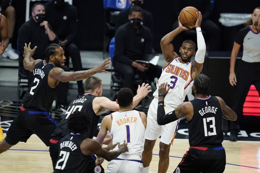 Phoenix Suns guard Chris Paul (3) passes over a group of Los Angeles Clippers defenders during the first half of an NBA basketball game Thursday, April 8, 2021, in Los Angeles. (AP Photo/Marcio Jose Sanchez)