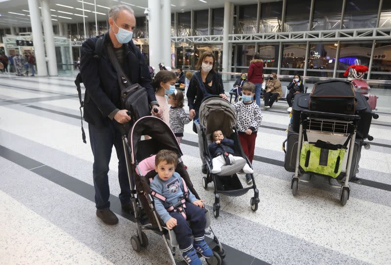 Dr. Fouad Boulos, Associate Professor of Clinical Pathology and Laboratory Medicine at the American University of Beirut (AUB) pushes a baby cart near his wife and children, at Beirut International airport