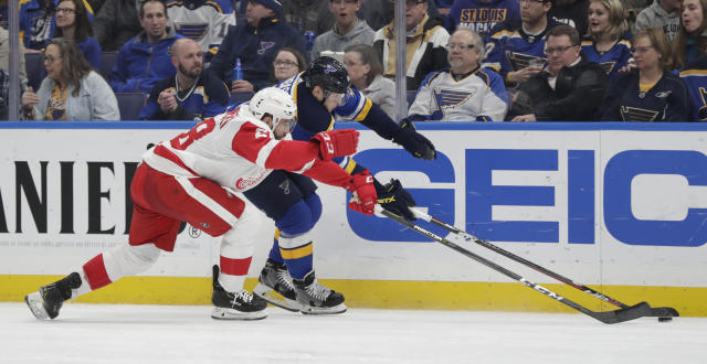 Detroit Red Wings' Luke Witkowski (28) tries to poke the puck away from St. Louis Blues' Ivan Barbashev (49) in the second period of an NHL hockey game, Thursday, March 21, 2019, in St. Louis. (AP Photo/Tom Gannam)