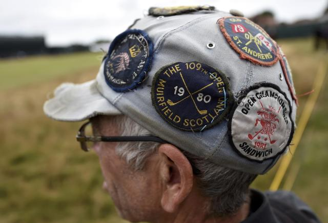 A spectator wearing a hat with golf badges watches play during a practice round ahead of the British Open Championship at the Royal Liverpool Golf Club in Hoylake, northern England July 16, 2014. REUTERS/Toby Melville (BRITAIN - Tags: SPORT GOLF)