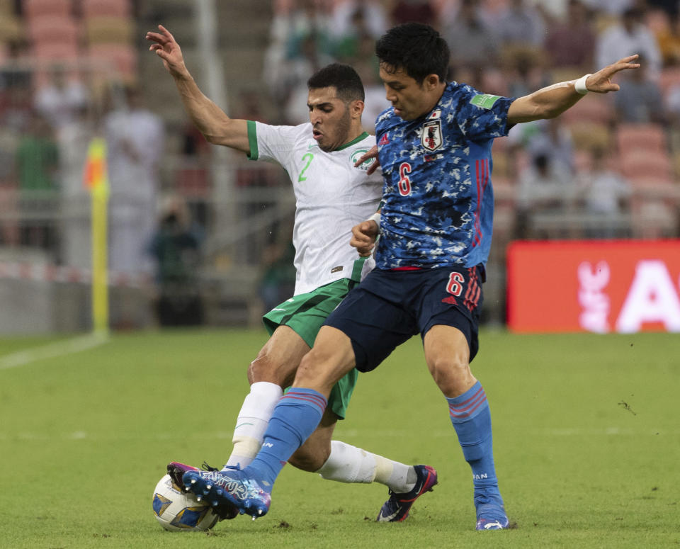 Japan's Wataru Endo, right, fights for the ball with Saudi Arabia's Sultan Al-Ghannam during their match of the Asian zone group B qualifying soccer match for the FIFA World Cup Qatar 2022 at the King Abdullah sports city stadium, in Jiddah, Saudi Arabia, Thursday, Oct. 7, 2021. (AP Photo)