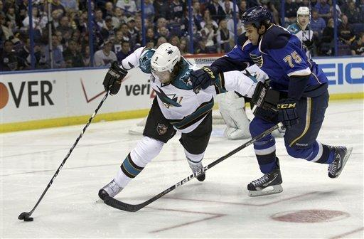 San Jose Sharks' Douglas Murray, left, of Sweden, controls the puck as St. Louis Blues' Ryan Reaves, right, defends during the second period of Game 1 of an NHL hockey first-round playoff series on Thursday, April 12, 2012, in St. Louis. (AP Photo/Jeff Roberson)