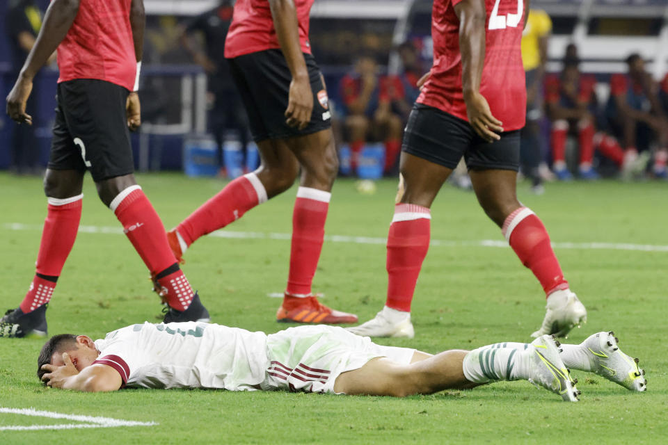 Mexico forward Hirving Lozano covers his bloodied eye during the first half of the team's match against Trinidad and Tobago in CONCACAF Gold Cup Group A in Arlington, Texas, Saturday, July 10, 2021. (AP Photo/Michael Ainsworth)