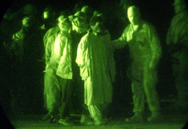 <p>U.S. Marines, shown through a night vision scope, escort battle field detainees into a detention center at Kandahar International Airport, Dec. 18, 2001. (Photo: USMC, Sgt. Thomas Michael Corcoran/Reuters) </p>