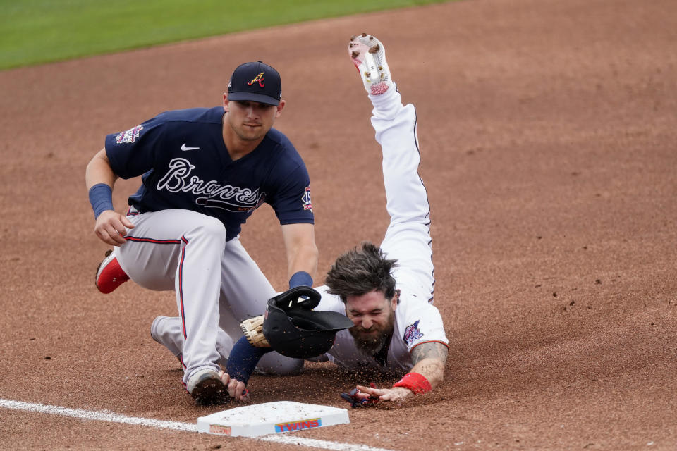 Minnesota Twins' Jake Cave, right, is tagged out by Atlanta Braves third baseman Austin Riley, left, at third base as he tries to advance on a teammates base hit in the second inning of a spring training baseball game against the Atlanta Braves Monday, March 22, 2021, in Fort Myers, Fla. (AP Photo/John Bazemore)
