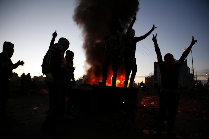 Palestinian protesters stand on a trash container during clashes with Israeli forces near an Israeli checkpoint in the West Bank city of Ramallah, following Trump's decision to recognize Jerusalem as Israel's capital
