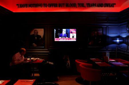 A man has lunch surrounded by pictures of former British PM Churchill as a TV screen shows Britain's PM Cameron speaking after Britain voted to leave the European Union at a British pub in Madrid