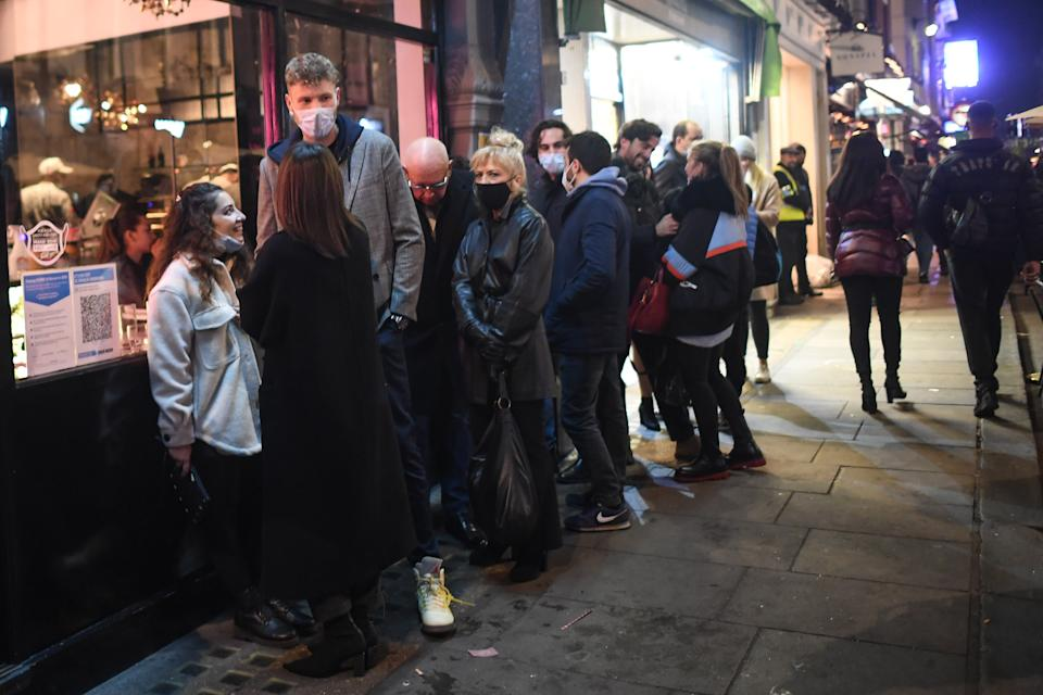 LONDON, ENGLAND - NOVEMBER 04: People are seen queuing outside a restaurant in Soho on November 4, 2020 in London, England. Non-essential businesses, including pubs and restaurants, will be forced to close from Thursday, Nov 5, following a new national lockdown in England. (Photo by Peter Summers/Getty Images)