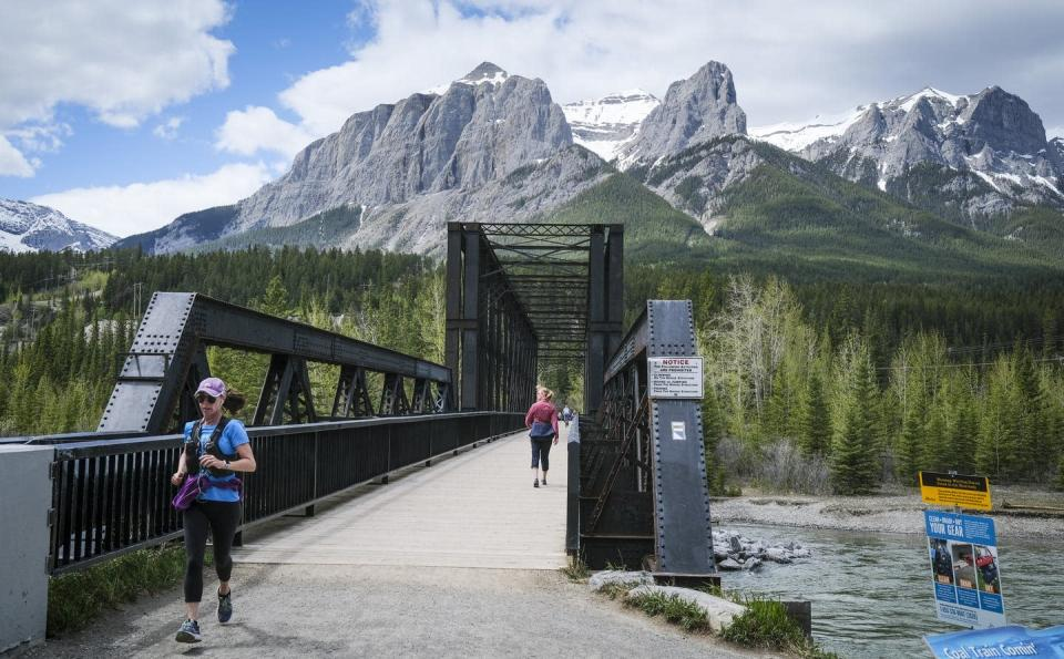 A woman runs on an old railway bridge with mountains in the background.