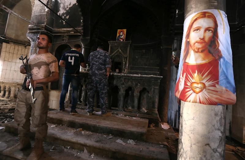 Iraqi Christian forces inspect the damage at the Church of the Immaculate Conception in the town of Qaraqosh, east of Mosul on October 30, 2016 (AFP Photo/Safin Hamed)