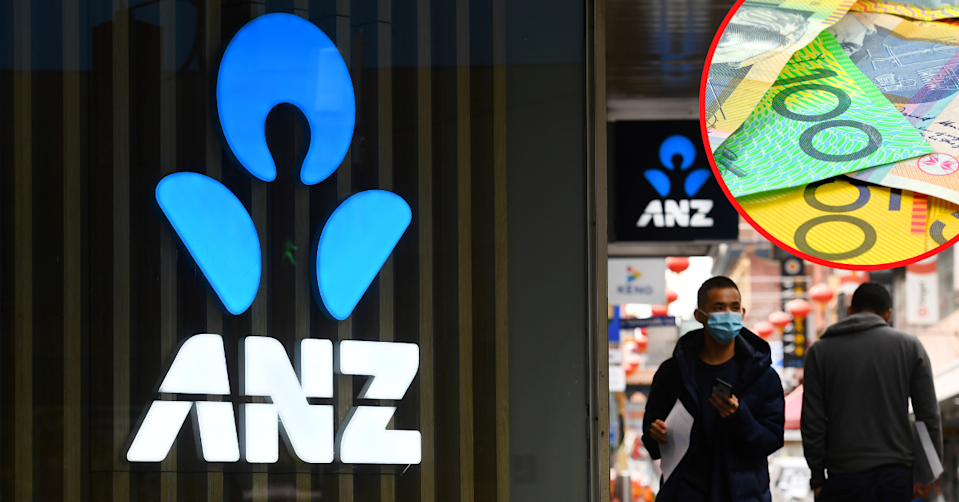 ANZ logo on. the side of a branch with people waling by in the street while wearing masks.