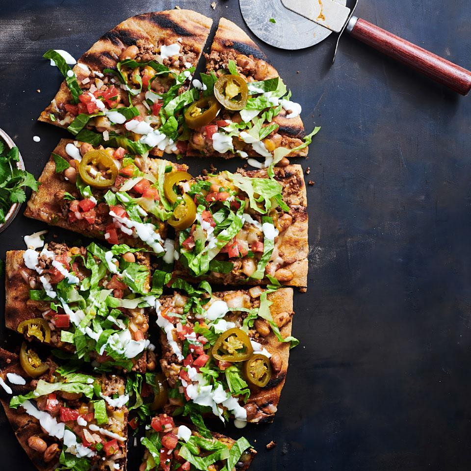 <p>Grilling pizza mimics the rustic flavor of a wood-fired oven. It cooks fast, though, so make sure you have all your ingredients prepped and ready to go for speedy flipping and topping. For this grilled pizza recipe we've topped the pie with classic taco toppings, including beans and salsa. Once you've mastered the method, you can use it as a template for how to grill pizza--just swap out the taco ingredients for your favorite toppings.</p>
