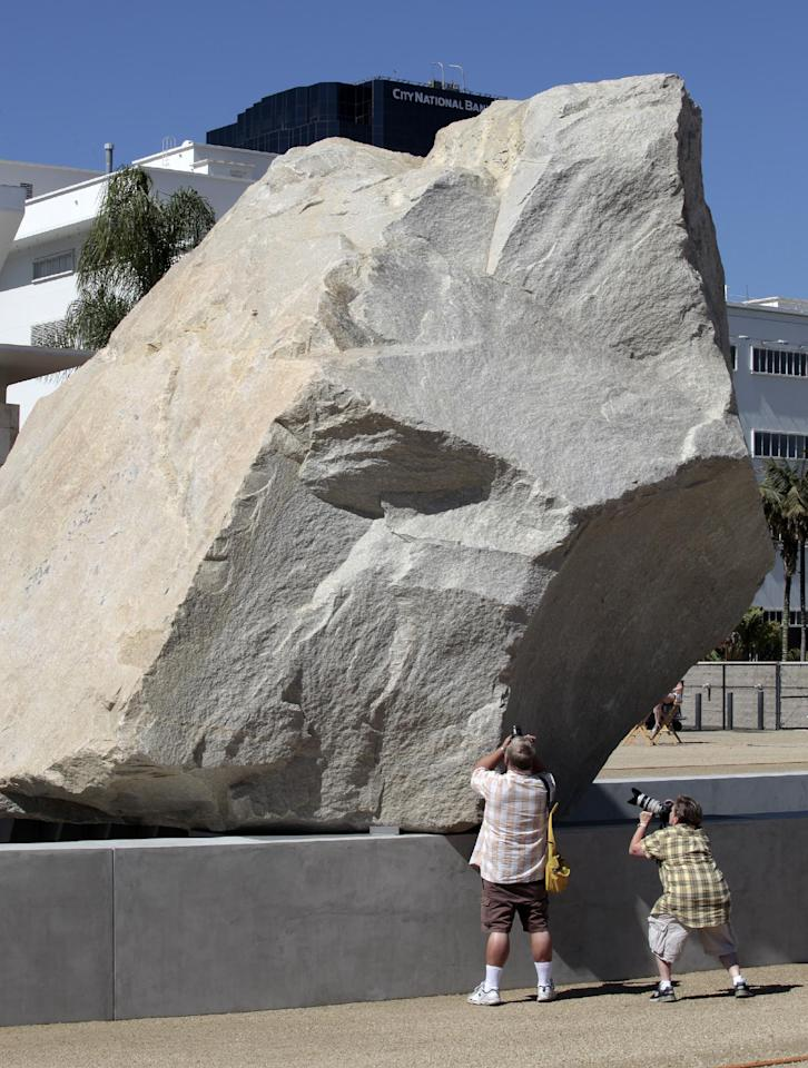 "Visitors take photos of Michael Heizer's ""Levitated Mass"" at the Los Angeles County Museum of Art in Los Angeles, on Sunday June 24,2012. Thousands showed up as the gigantic work was unveiled on the museum's rear lawn, where it is intended to remain forever. (AP Photo/Richard Vogel)"