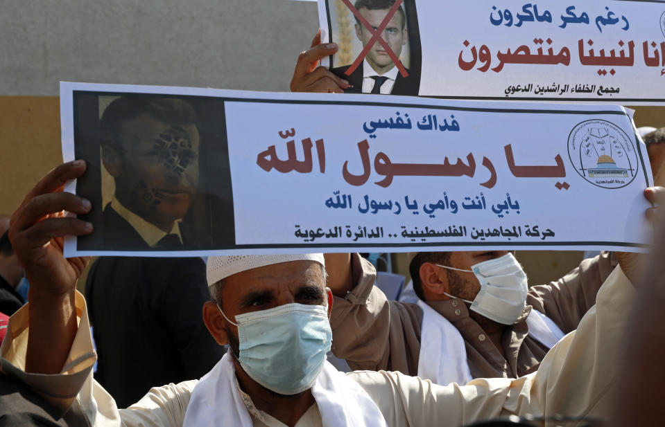 "Islamic scholars hold defaced pictures of French President Emmanuel Macron during a protest against the publishing of caricatures of the Prophet Muhammad they deem blasphemous, in front of the French Cultural center in Gaza City, Monday, Oct. 26, 2020. Arabic reads: ""Despite Macron's malice, we rise up to our Prophet"" and ""I sacrifice myself, my father and mother for you Prophet."" (AP Photo/Adel Hana)"
