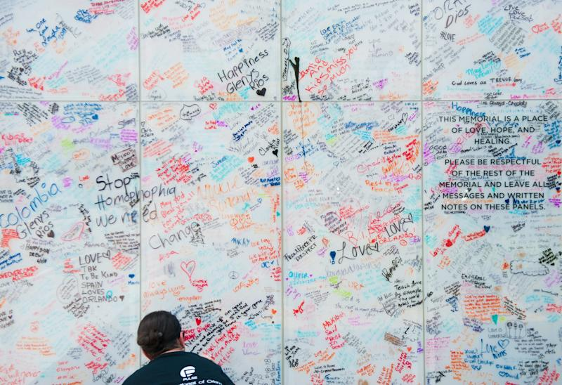 Angie Sola, a volunteer with Disney, leaves a message on the Pulse sign at the memorial. (Chris McGonigal/HuffPost)