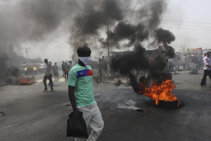 """FILE- An Unidentified man stands near burning tyres during a protest on a major road junction in the commercial capital of Lagos, Nigeria, during a fuel subsidy protest in this file photo dated Tuesday, Jan. 3, 2012, as angry mobs call on the government to keep a cherished consumer subsidy that had kept gas affordable for more than two decades. A 30-minute film documentary called """"Fuelling Poverty"""" has been online for months, but it is revealed Sunday April 21, 2013, that Nigerian officials have refused its director Ishaya Bako permission to show it publicly in this oil-rich nation, as it focuses on the January 2012 protests and the alleged billions of dollars thought to have been swallowed up by greedy companies and the nation's elite. (AP Photo/Sunday Alamba, File)"""