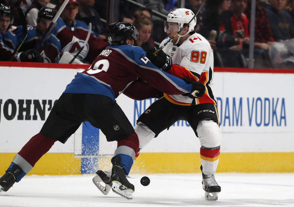 Colorado Avalanche defenseman Samuel Girard, left, hits Calgary Flames left wing Andrew Mangiapane as he brings the puck up the ice in the second period of an NHL hockey game Monday, Dec. 9, 2019, in Denver. (AP Photo/David Zalubowski)