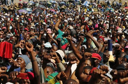 Lonmin workers on strike react as they listen to President of South Africa's AMCU Joseph Mathunjwa at the Wonderkop stadium in Nkaneng township outside the Lonmin mine in Rustenburg