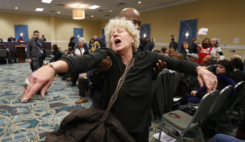 FILE - In this Jan. 8, 2019, file photo, a protester gets escorted out of a meeting of the Virginia State Air Quality Control Board by State Police in Richmond, Va. The U.S. Supreme Court is set to wade into a long-running battle between developers of a 605-mile natural gas pipeline and environmental groups who oppose the pipeline crossing the storied Appalachian Trail. On Monday, Feb. 24, 2020, the high court will hear arguments on a critical permit needed by developers of the Atlantic Coast Pipeline. (AP Photo/Steve Helber, File)