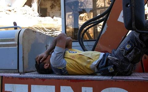 A member of the Syrian civil defence, known as the White Helmets, rests atop an excavator after participating in a search for victims under the rubble of buildings, - Credit: ABDULAZIZ KETAZ/AFP/Getty Images
