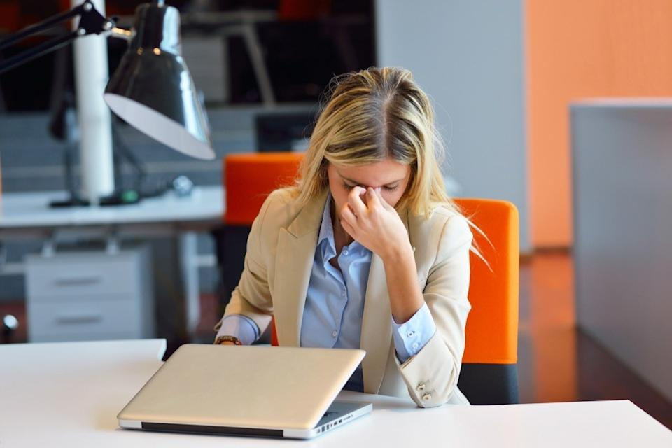 frustrated woman in office in front of laptop