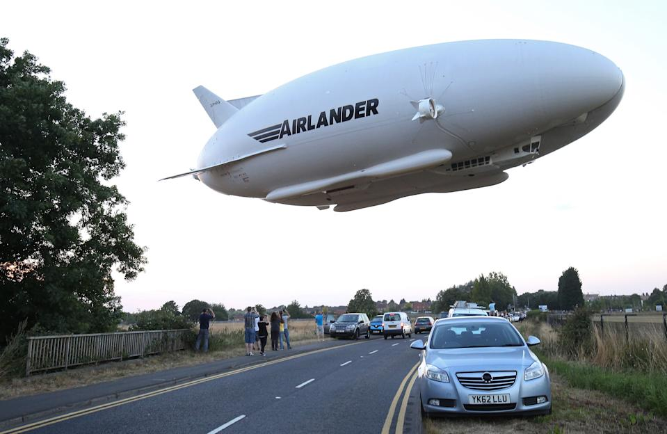 TOPSHOT - The Hybrid Air Vehicles HAV 304 Airlander 10 hybrid airship is seen in the air over a road on its maiden flight from Cardington Airfield near Bedford, north of London, on August 17, 2016.  The Hybrid Air Vehicles 92-metre long, 43.5-metre wide Airlander 10, billed as the world's longest aircraft, lifted off for the first time from an airfield north of London. The Airlander 10 has a large helium-filled fabric hull and is propelled by four turbocharged diesel engines. According to the company it can stay airborne for up to five days at a time if manned, and for over 2 weeks unmanned with a cruising speed of just under 150 km per hour and a payload capacity of up to 10,000 kg. / AFP / JUSTIN TALLIS        (Photo credit should read JUSTIN TALLIS/AFP via Getty Images)