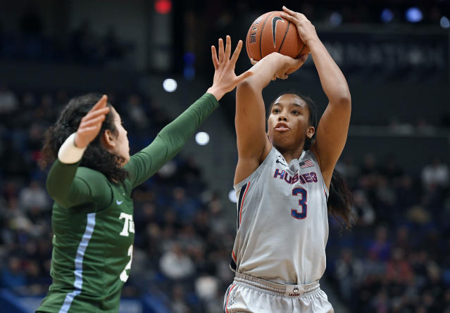 FILE - In this Wednesday, Feb. 19, 2020, file photo, Connecticut's Megan Walker, right, shoots over Tulane's Irina Parau in the second half of an NCAA college basketball game, in Hartford, Conn. Walker has submitted paperwork to enter the WNBA draft, which is scheduled to be held April 17, 2020. (AP Photo/Jessica Hill, File)