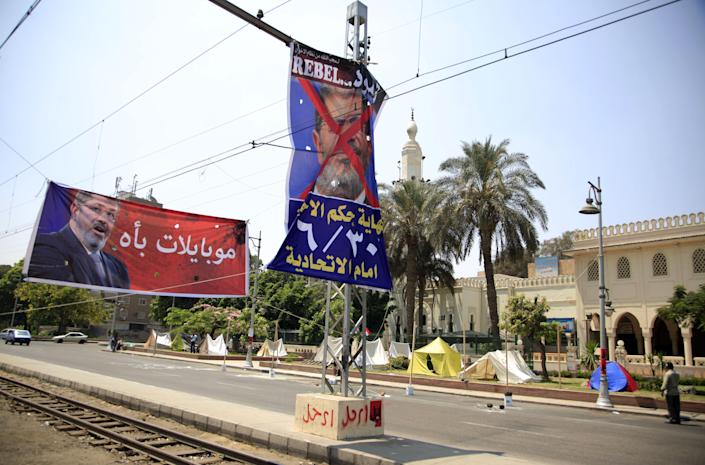 """A poster of Egypt's Islamist President Mohammed Morsi with Arabic that reads, """"The end of the reign of terror,"""" hangs on the side of the street next to the presidential palace in Cairo, Egypt, Saturday, June 29, 2013. As the streets once again fill with protesters eager to oust the president and Islamists determined to keep him in power, Egyptians are preparing for the worst: days or weeks of urban chaos that could turn a loved one into a victim. Households already beset by power cuts, fuel shortages and rising prices are stocking up on goods in case the demonstrations drag on. Businesses near protest sites are closing until crowds subside. Fences, barricades and walls are going up near homes and key buildings. And local communities are organizing citizen patrols in case security breaks down. (AP Photo/Khalil Hamra)"""