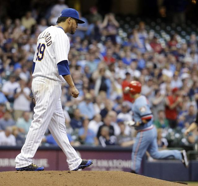 Milwaukee Brewers starting pitcher Yovani Gallardo walks back to the mound as Minnesota Twins' Josh Willingham rounds the base after Willingham hit a three-run home run during the third inning of a baseball game Tuesday, June 3, 2014, in Milwaukee. (AP Photo/Morry Gash)