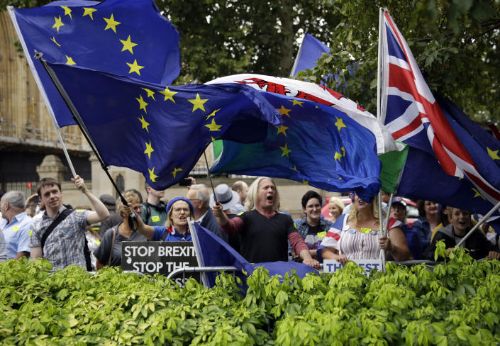 Anti-Brexit supporters wave flags and hold signs at College Green near the Houses of Parliament in central London, Wednesday, Aug. 28, 2019. British Prime Minister Boris Johnson maneuvered Wednesday to give his political opponents even less time to block a no-deal Brexit before the Oct. 31 withdrawal deadline, winning Queen Elizabeth II's approval to suspend Parliament. (AP Photo/Matt Dunham)