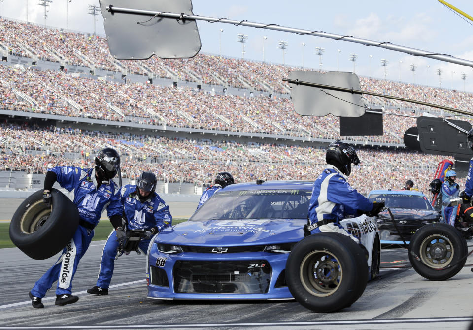 Alex Bowman's crew changes tires during a pit stop in a NASCAR Daytona 500 auto race at Daytona International Speedway, Sunday, Feb. 17, 2019, in Daytona Beach, Fla. (AP Photo/Terry Renna)