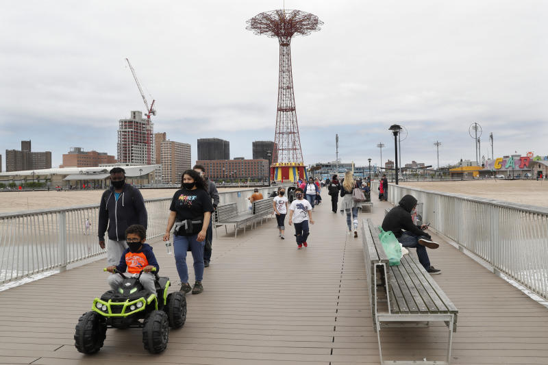 A youngster rides a toy electric vehicle on the pier at Coney Island beach during the current coronavirus outbreak, Sunday, May 24, 2020, in New York. The parachute jump is seen in the background. (AP Photo/Kathy Willens)