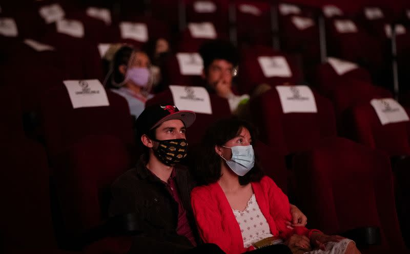 """Moviegoers sit socially distanced as they wait for the movie """"Godzilla vs. Kong"""" on the reopening day of the TCL Chinese theatre during the outbreak of the coronavirus disease (COVID-19), in Los Angeles"""