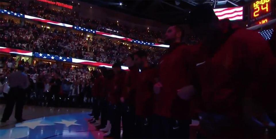 Members of the Cleveland Cavaliers stand and lock arms during the national anthem before their season opener against the Boston Celtics. (Screencap via Sports Illustrated)