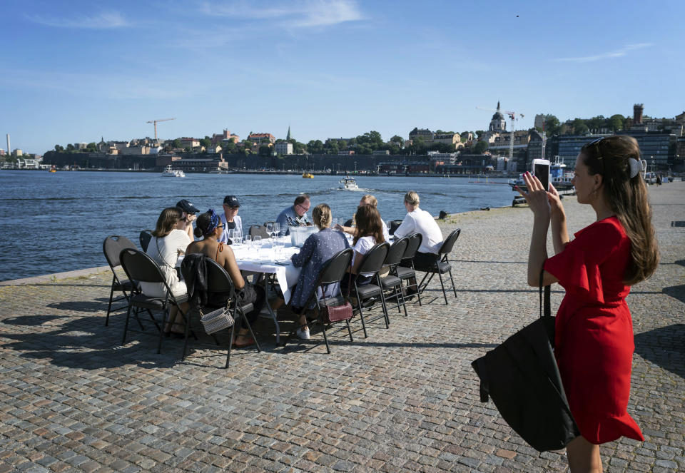 FILE - In this Friday, June 26, 2020 file photo employees socially distance due to the coronavirus as they have a drink after work, in Stockholm. Sweden's relatively low-key approach to coronavirus lockdowns captured the world's attention when the pandemic first hit Europe. Now, as infection numbers surge in much of Europe, Sweden has some of the lowest numbers of new cases and there are only 14 people being treated for the virus in intensive care in the country of 10 million. (Stina Stjernkvist/TT News Agency via AP, File)
