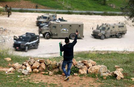 Palestinian protester holds up an unspent tear gas grenade fired by Israeli troops as he stands in front of the troops during clashes, near Israel's Ofer Prison, near the West Bank city of Ramallah