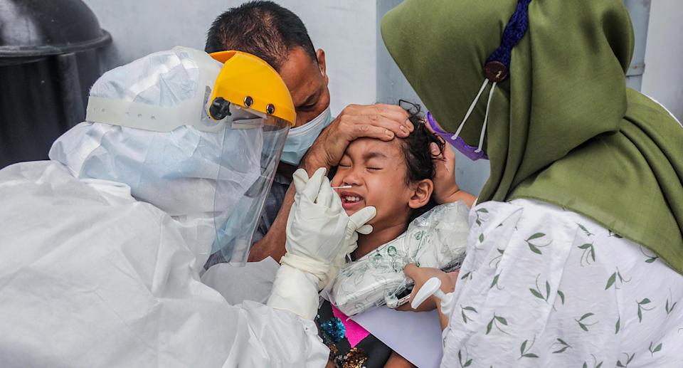 A healthcare worker in a hazmat suit collects specimen samples from a girl during a COVID-19 swab test in Medan, North Sumatra, Indonesia, 26 April 2021. Indonesia has banned foreign travelers from India over the Covid-19 scare, official said. Indonesia has recorded more than 1,600,000 coronavirus disease (COVID-19) cases since the beginning of the pandemic.  EPA/DEDI SINUHAJI
