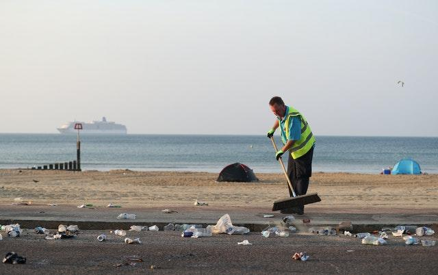 The clean-up gets under way after a busy Saturday on the beach