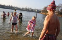 """Members of the Berliner Seehunde (Berlin Seals) ice swimmers club walk out of the water after they took a dip in Lake Orankesee during their traditional New Year swimming event in Berlin, January 1, 2015. The words on the helmet (L, front) reads """"The Berlin Brandenburg international airport BER is totally unsuccessful."""" REUTERS/Fabrizio Bensch (GERMANY - Tags: SOCIETY SPORT SWIMMING)"""