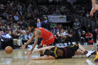 Chicago Bulls' Coby White (0) and Cleveland Cavaliers' Matthew Dellavedova (18) scramble for the ball during the second half of an NBA basketball game Tuesday, March 10, 2020, in Chicago. Chicago won 108-103. (AP Photo/Paul Beaty)