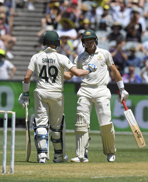 Australia's Steven Smith, left, congratulates team mate Marnus Labuschagne, right, after his 50 runs during play in the cricket test match against New Zealand in Melbourne, Australia, Thursday, Dec. 26, 2019. (AP Photo/Andy Brownbill)