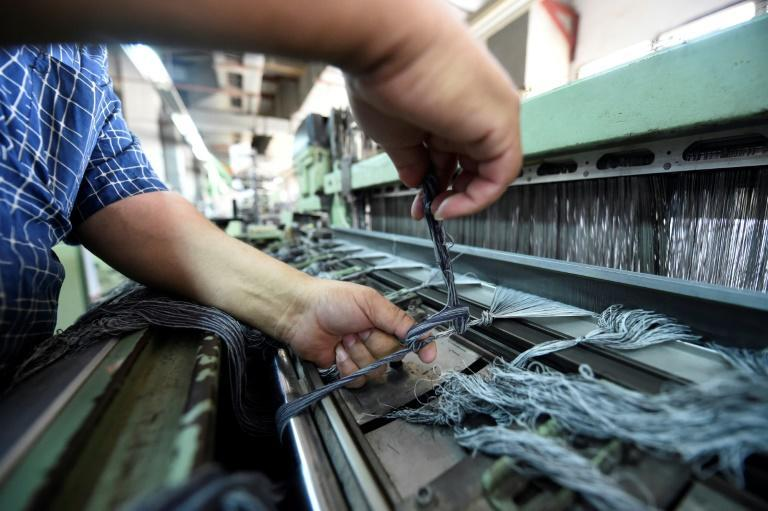 A worker prepares high-quality long-fibre cotton threads at the Marie Louis clothing and textile factory
